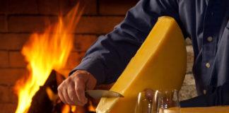 Raclette-Käse wird am Feuer erhitzt und auf den Teller geschabt.