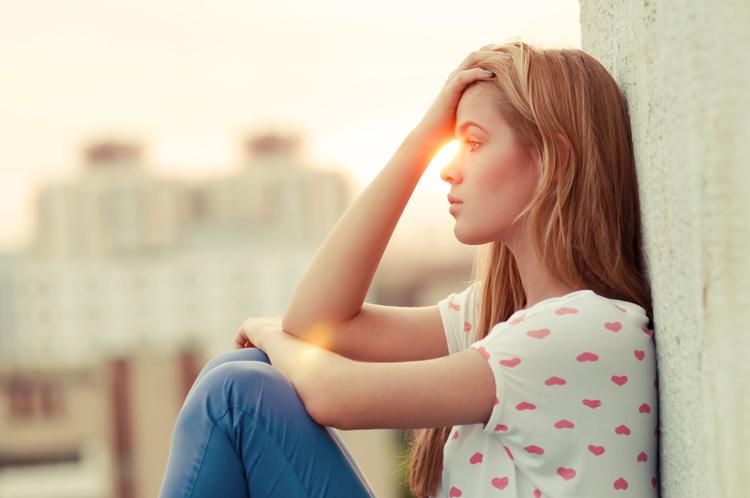 Eine Frau sizt an der Wand und sollte richtig atmen