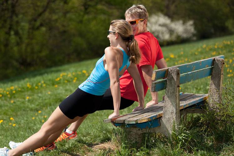 Ein Paar auf einer Bank im freien beim Durchatmen. Richtiges Atmen beim Sport ist wichtig.