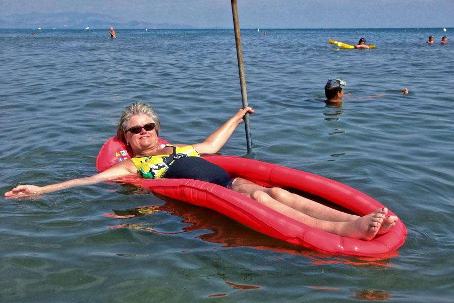 Eine Urlauberin entspannt sich auf der Luftmatratze und geniesst den Rollstuhlurlaub