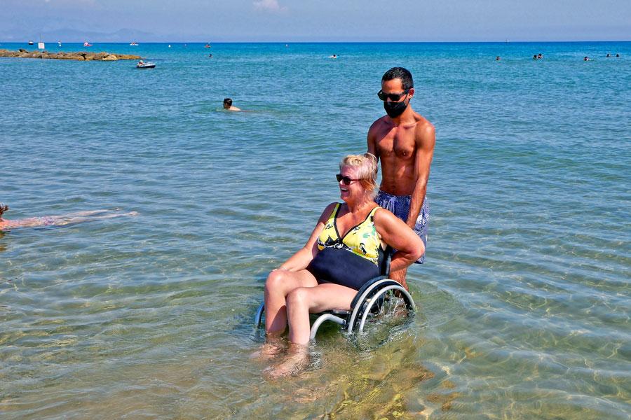 Ein Helfer fährt eine Rollstuhlurlauberin ins Meer