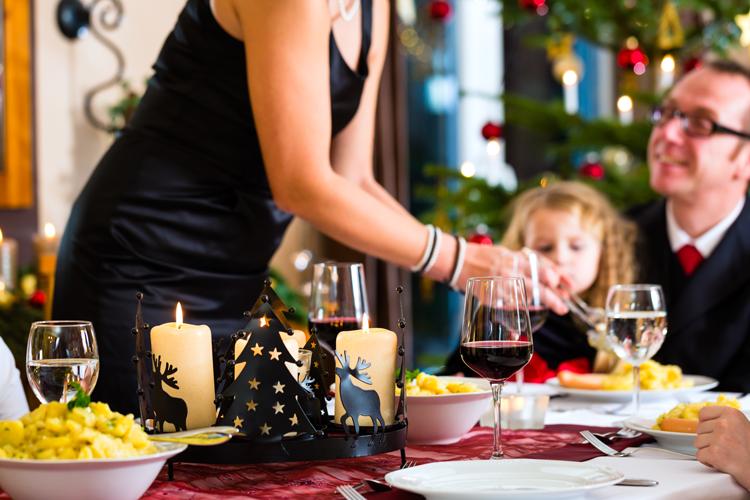 Festlich gedeckter Tisch, Frau schöpft Mann und Kind, Hintergrund ein Weihnachtsbaum