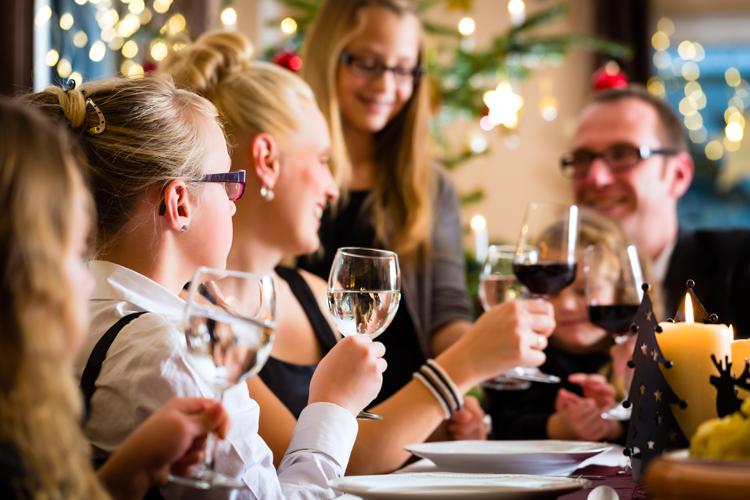Menschen am Tisch prosten sich zu, die einen mit Wein, die andern Wasser - Abnehmen, Alkohol in Maßen trinken