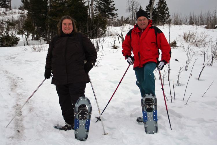 Mann und Frau mit Schneeschuhen, Bewegung über die Festtage hilft abnehmen