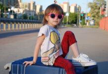 Mädchen sitzt auf dem Koffer und ist bereit für die Autofahrt