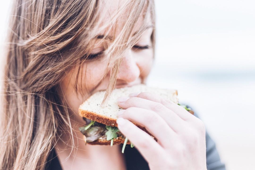 Junge Frau beisst herzhaft in ein Sandwich