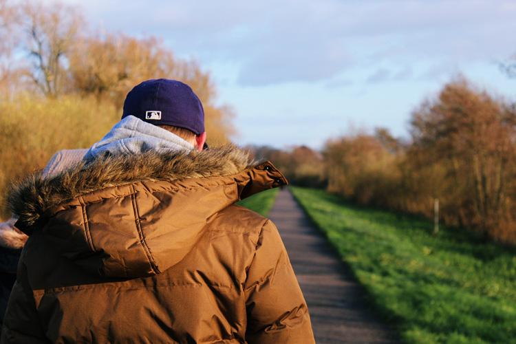 Mensch spaziert bei Sonnenschein Weg entlang