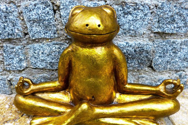 Goldige Froschskulptur, die in Yoga-Stellung meditiert