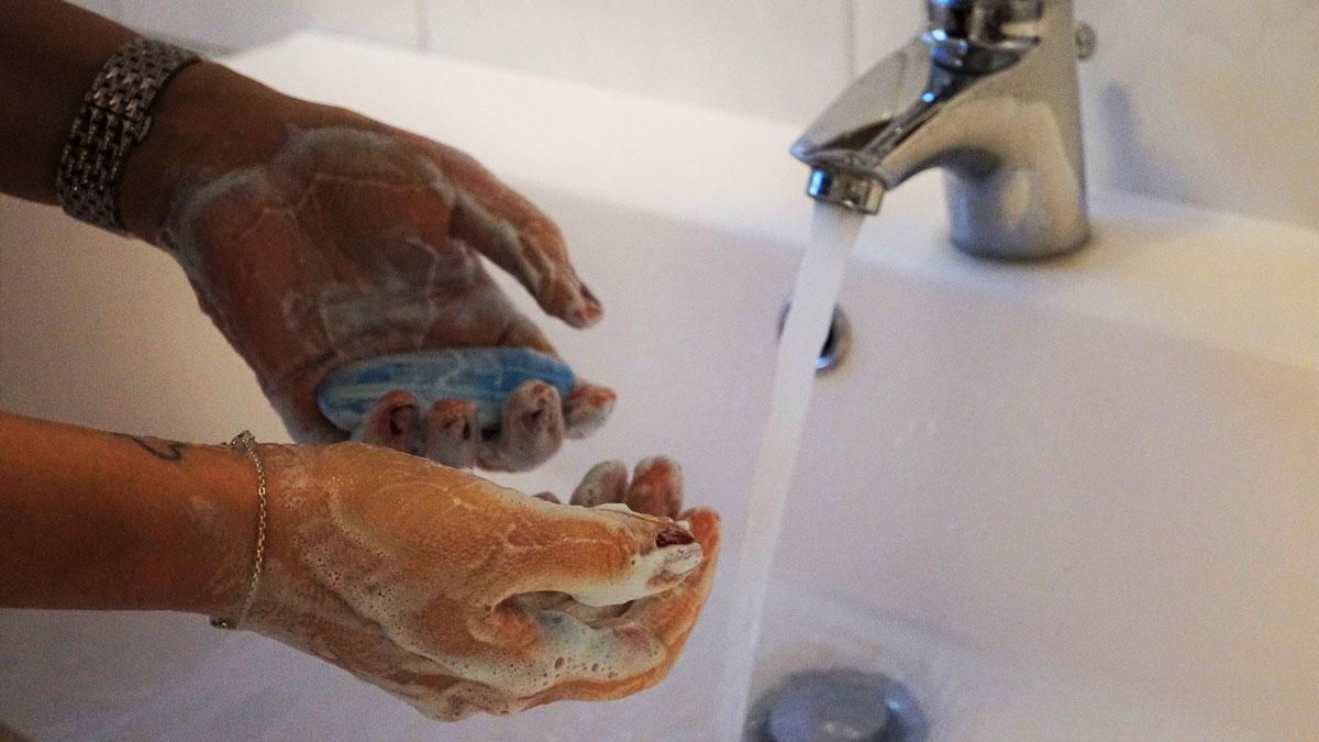 Eine Frau wäscht ihre Hände gründlich mit Seife.