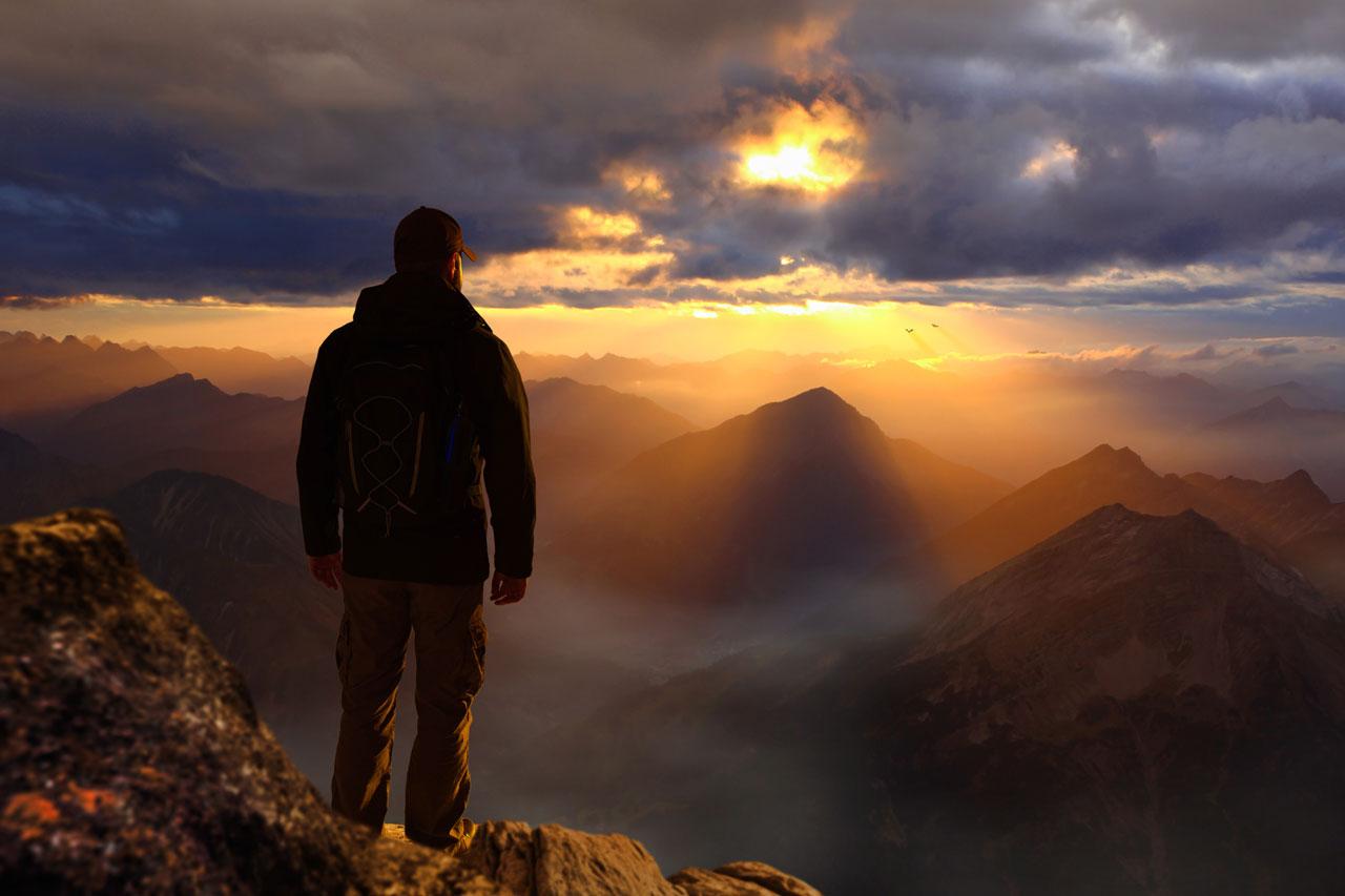 Mann auf Berggipfel: Dranbleiben und den Erfolg geniessen