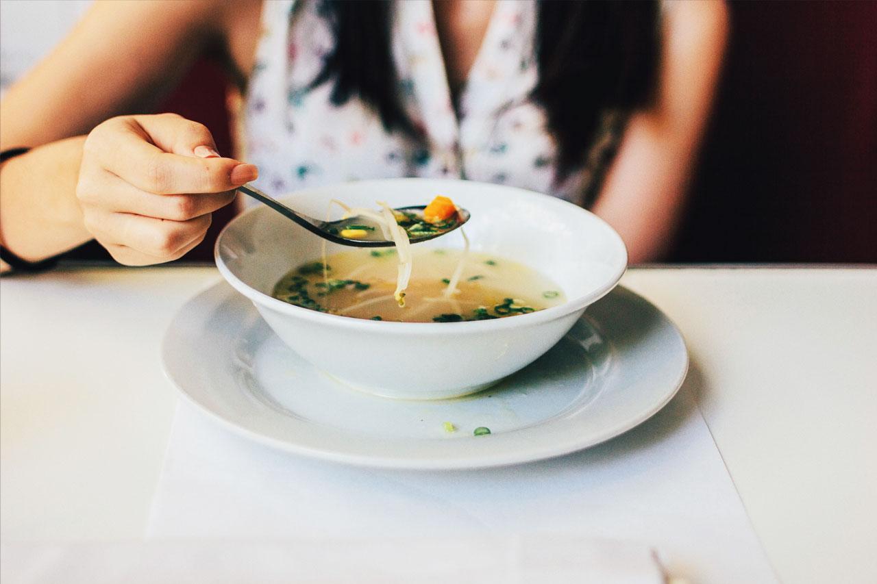 Frau isst Gemüsesuppe