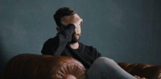Ein gestresster Mann sitzt auf dem Sofa