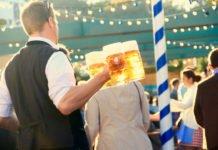 Die Bedinung am Münchner Oktoberfest bringt mehrere Maßkrüge Bier an den Tisch