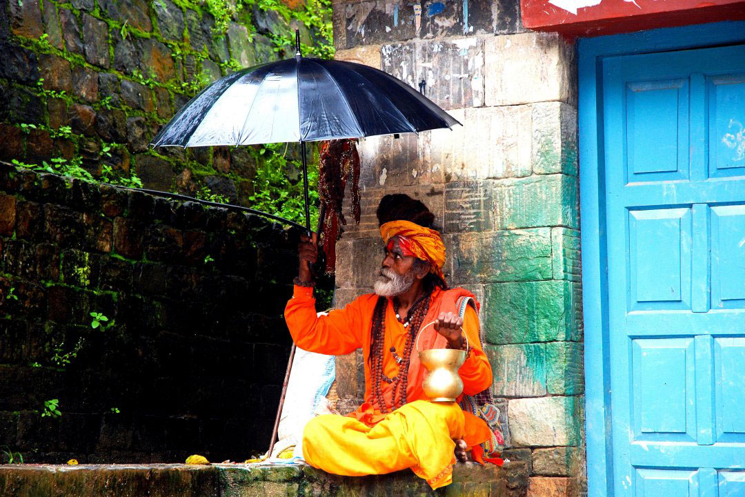 Indischer Guru mit Schirm