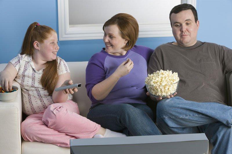 Übergewichtige Familie auf Sofa