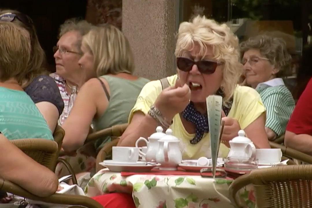 Frau ist im Strassen-Café isst ein Stück Kuchen