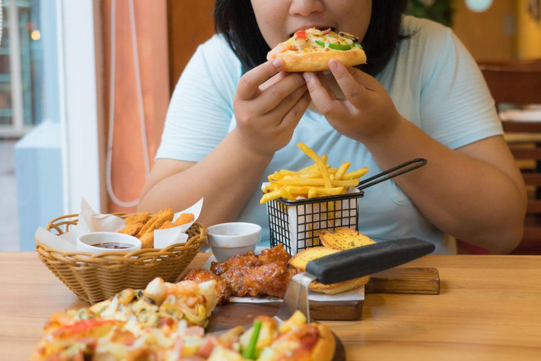 Frau sitzt am Tisch und isst sich durch verschiedene Fertigmahlzeiten