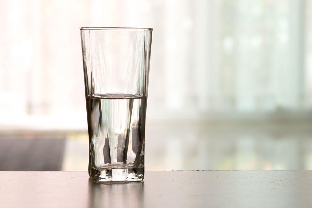 Halbleeres Wasserglas auf den Tisch