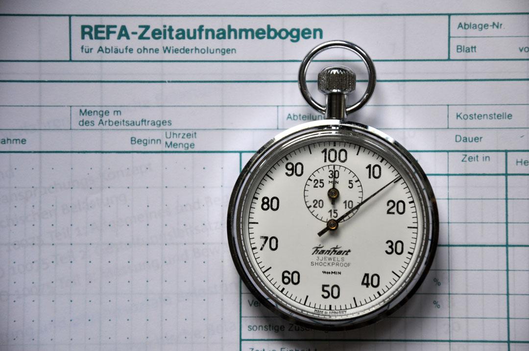 """Traditionelle, mechanische """"REFA-Stoppuhr"""" in HM-Teilung vor Zeitaufnahmebogen"""