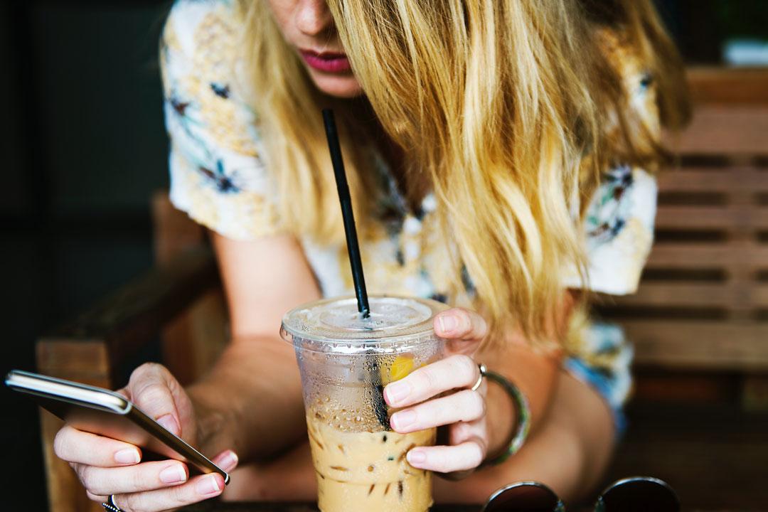 Eiskaffee trinken mit Smartphone in der Hand