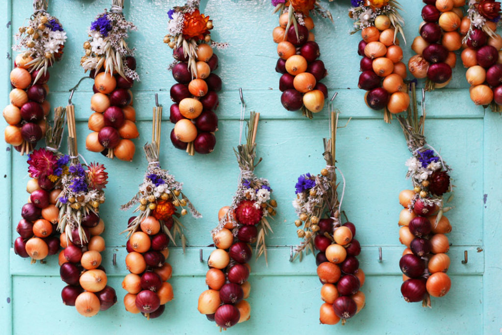 Verschiedene Zwiebelzöpfe hangen an Haustür .