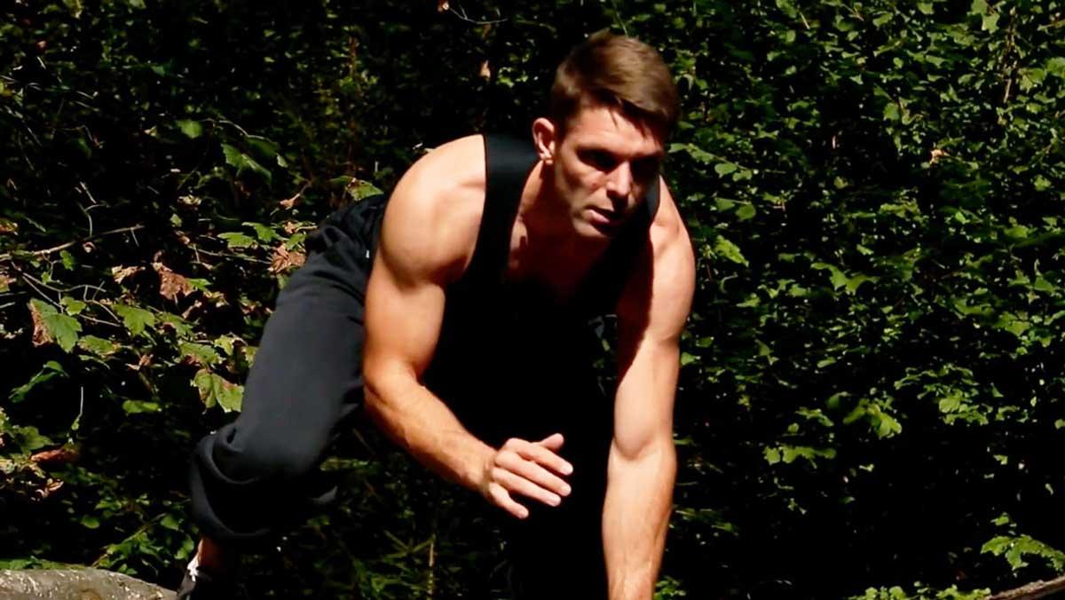 Ein Fitnesstrainer zeigt im Freiien Animal Movement