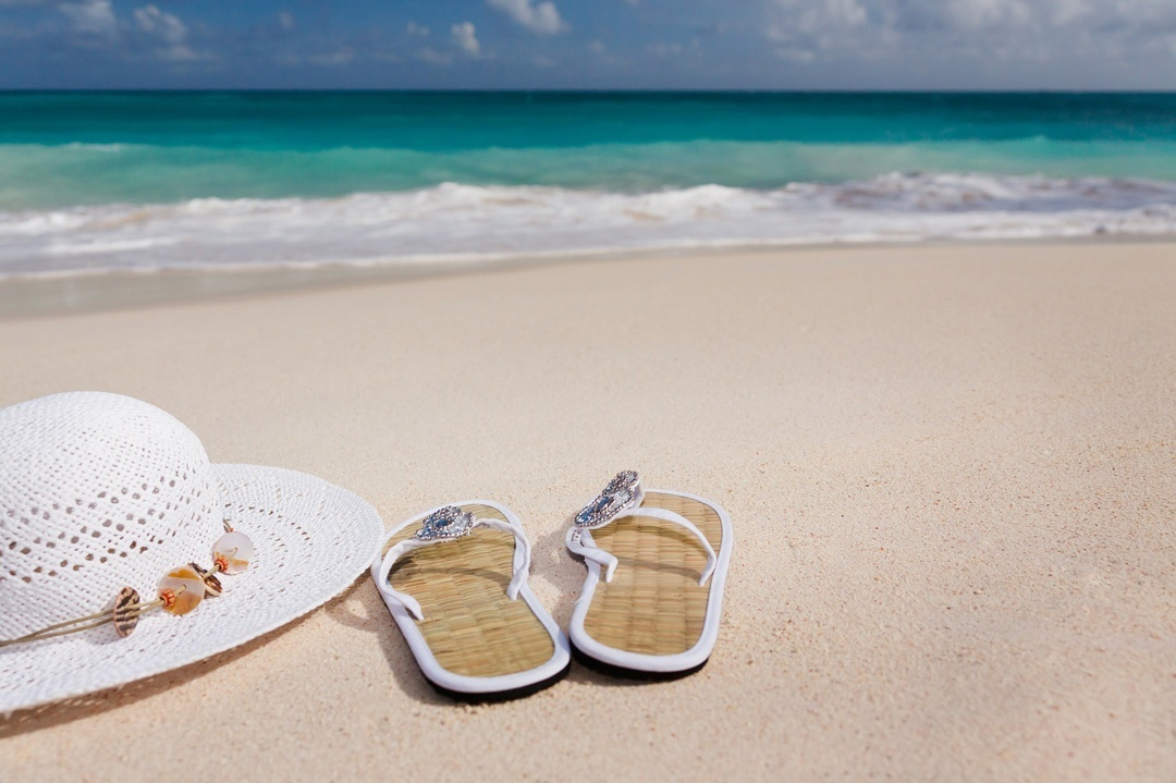 Weisser Hut und Flip-Flops am Strand