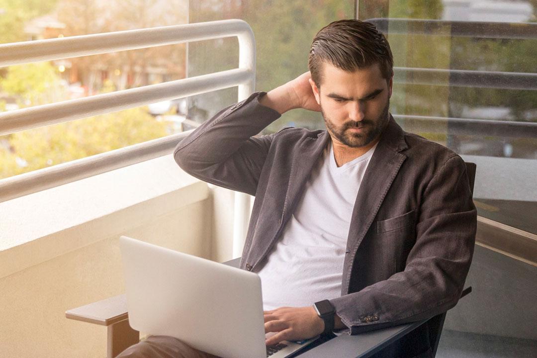 Geschäftsmann mit Laptop auf Balkon