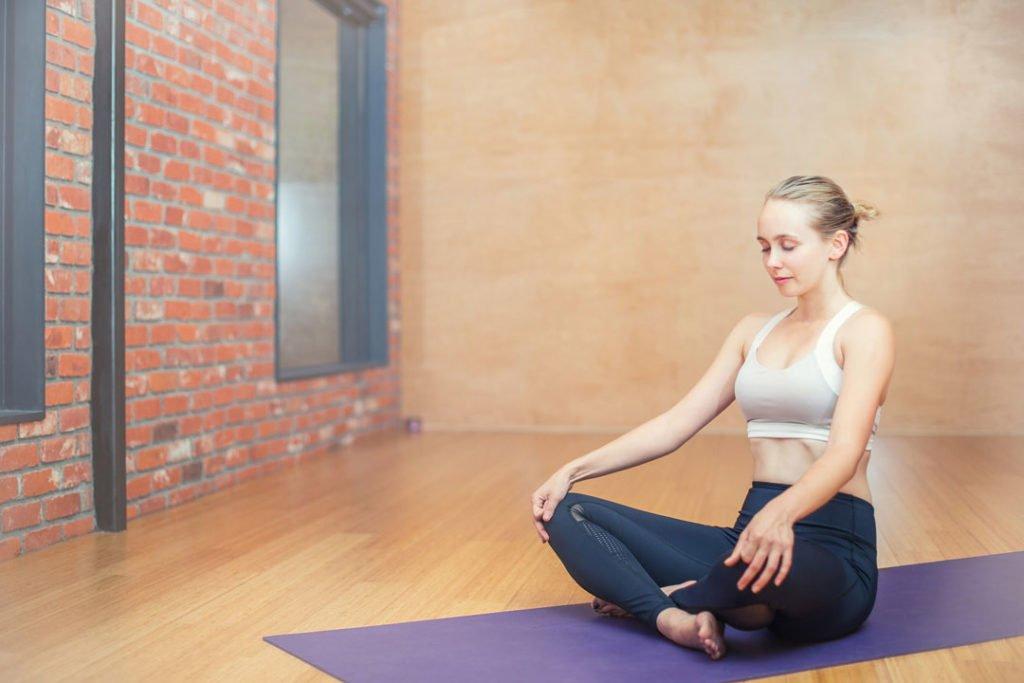 Eine Frau macht Yogaübungen und verbessert ihre Körperwahrnehmung