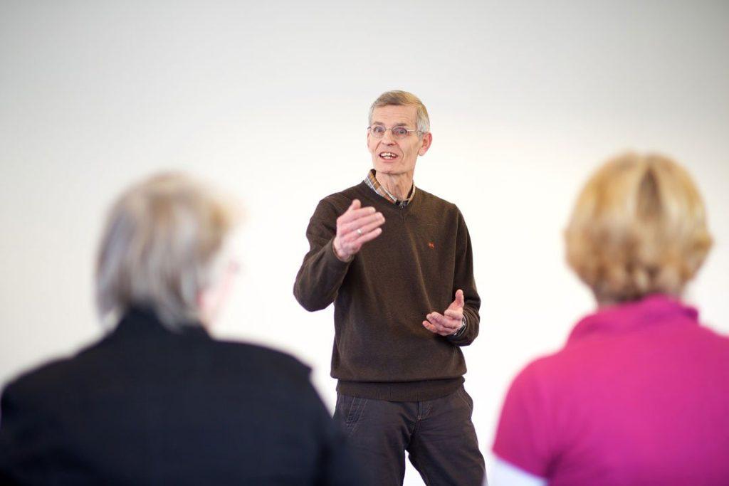 Ein Coach berät zwei Personen in einem Vortrag