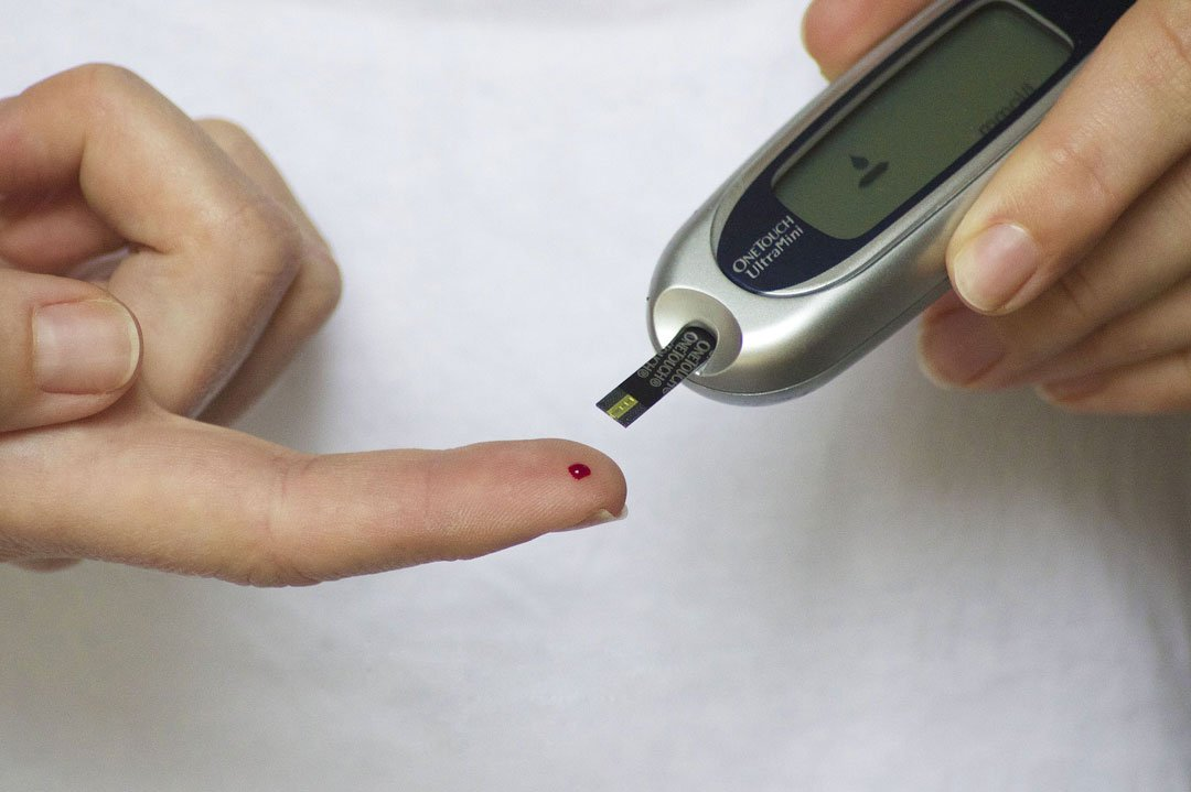 Blutzucker wird mit einem Messgerät am Finger gemessen