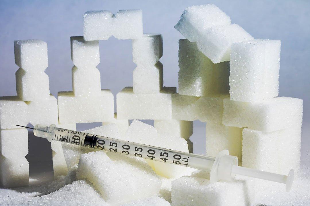 Würfelzucker und Insulinspritze