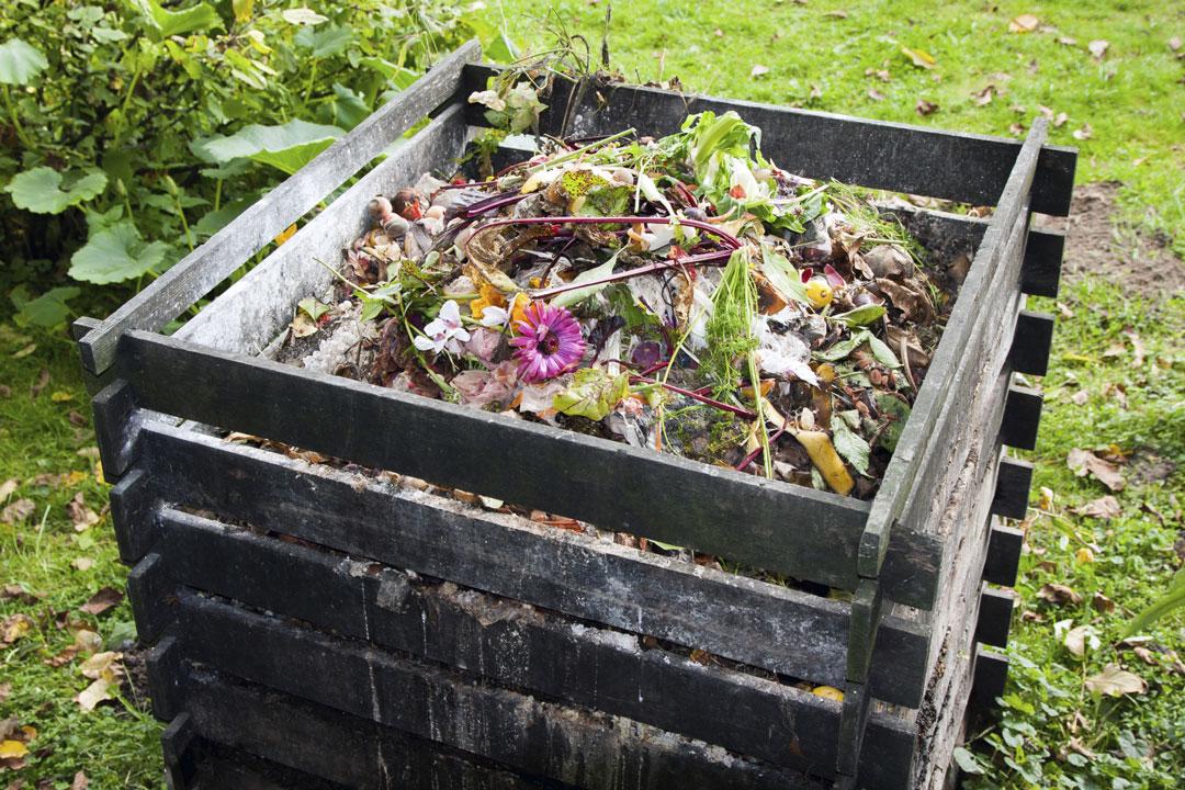 Ein Komposthaufen aus Holz im Garten