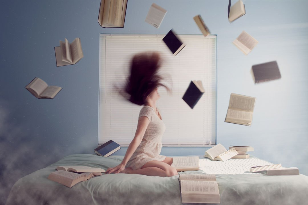 Junge Frau auf dem Bett mit vielen fliegenden Lernbücher