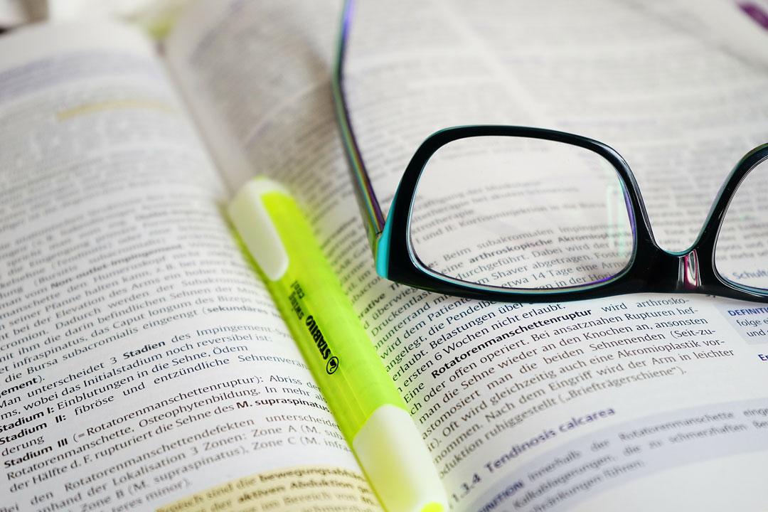Lernbuch mit Lesebrille und gelben Marker