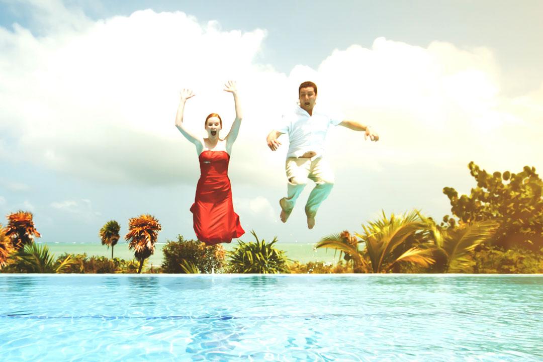 Ein Paar springt bekleidet in den Swimmingpool