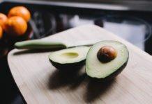 Avocado in zwei Hälften auf einem Holzbrett