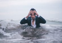 Ein Mann steht bis zum Oberkörper im Wasser und weiss nicht weiter