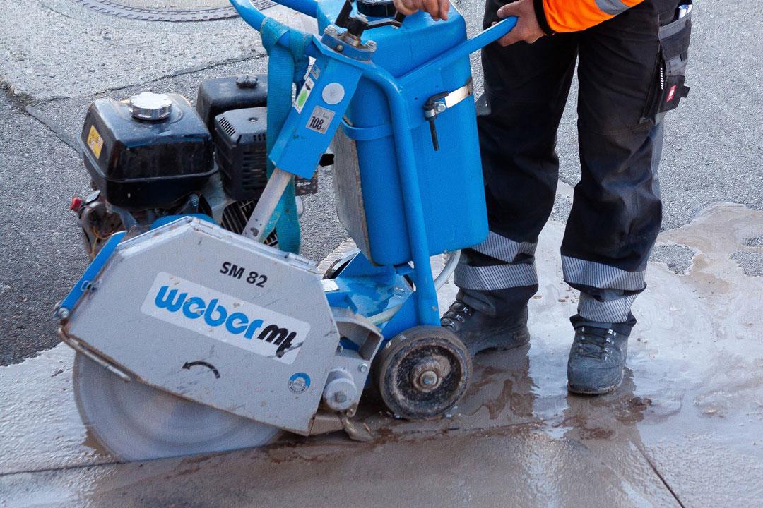 Mann arbeitet mit einer Schneidemaschine auf der Baustelle