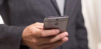 Mann im Anzug bedient sein Smartphone