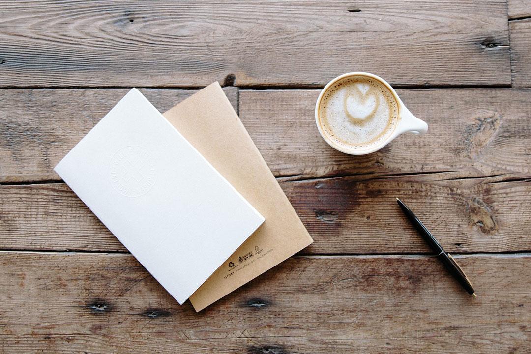 Papier, Kugelschreiber mit einem Kaffee auf dem Tisch.