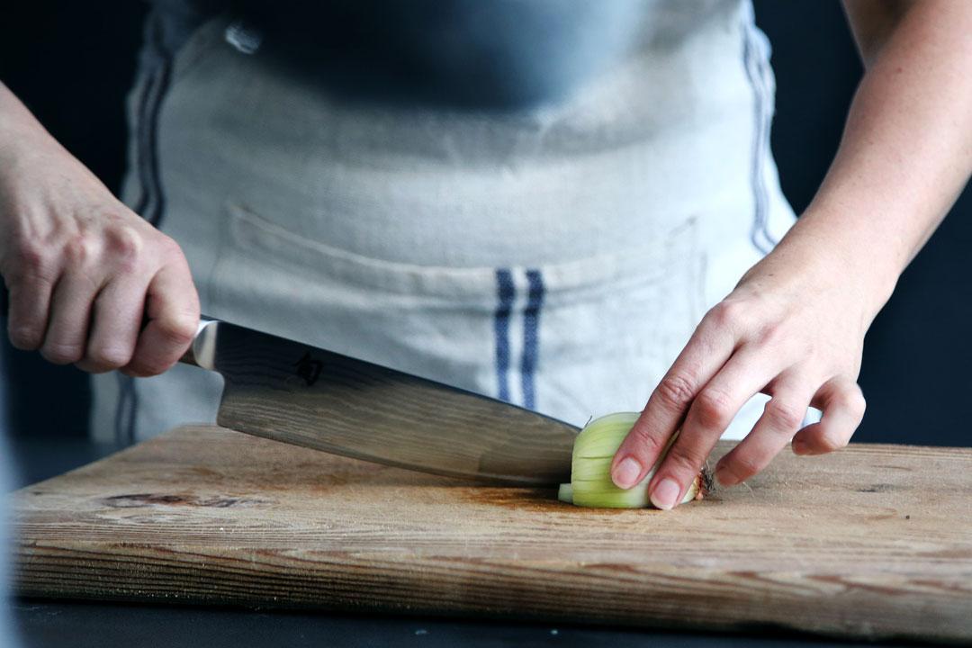 Köchin scheidet Zwiebel auf einem Hpolzbrett