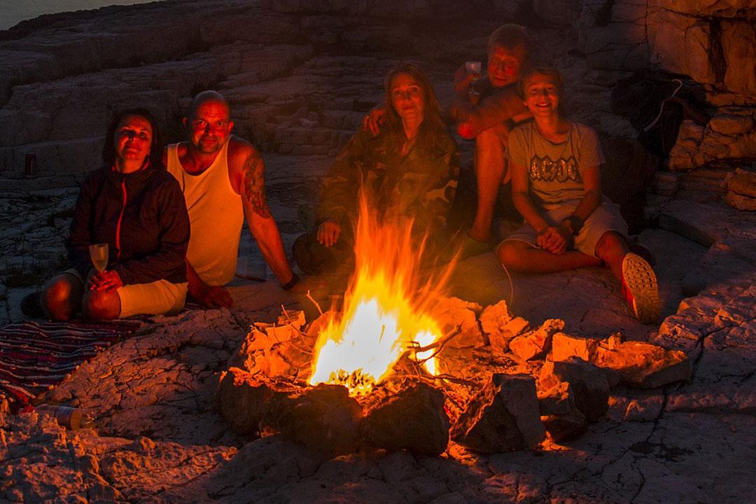 Jugentliche sitzen zusammen am Lagerfeuer