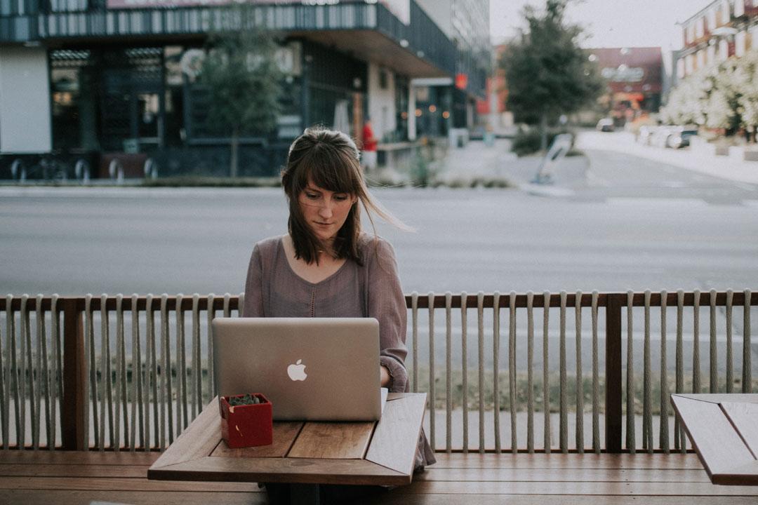 Ein junge Unternehmerin arbeitet im Freien am Laptop