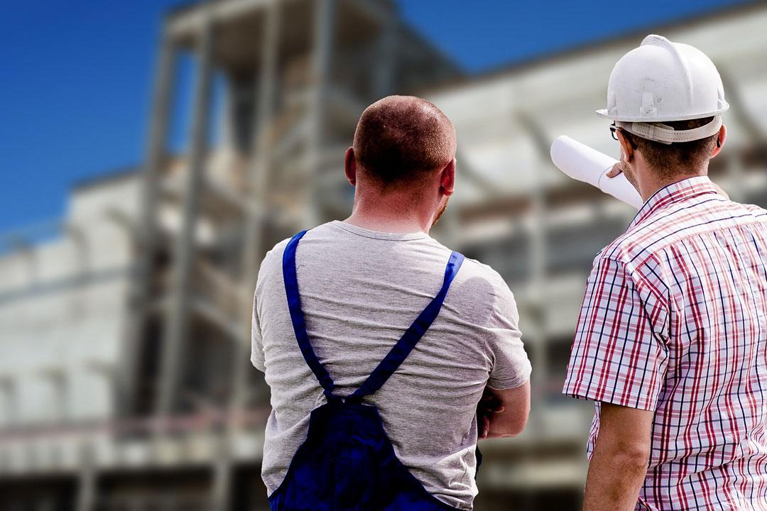 Zwei Arbeiter stehen vor der Baustelle