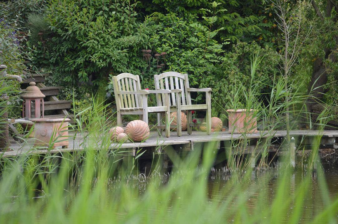 Garten mit zwei Stühlen vor dem Teich