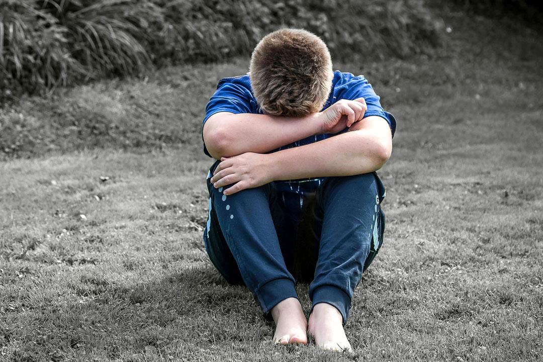 Junge Person fühlt sich durch innere Leere einsam und sitzt im Freien auf dem Boden