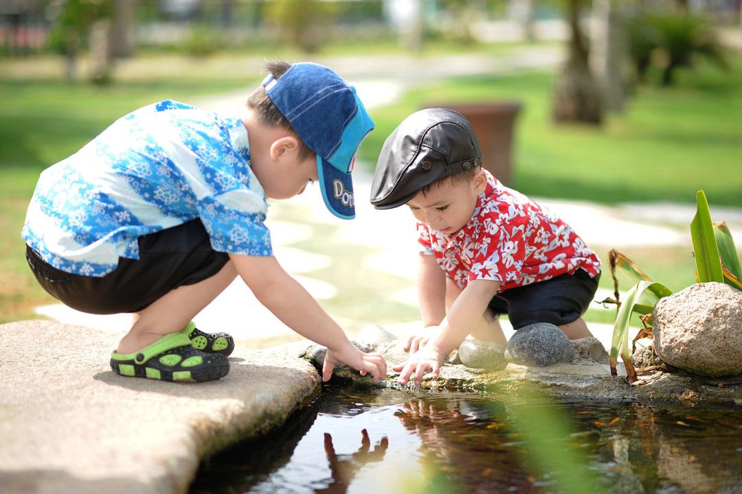 Zwei Kleinkinder spielen gemeinsam am Gartenteich