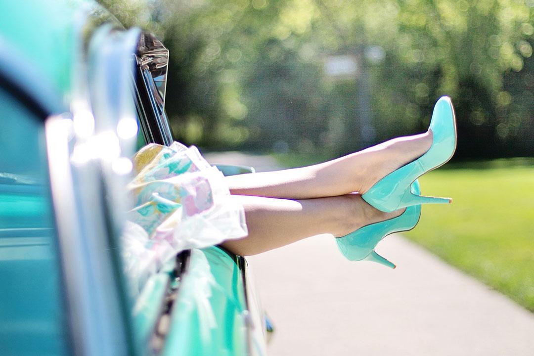 Frauenbeine aus dem Fenster eines Oldtimer halten