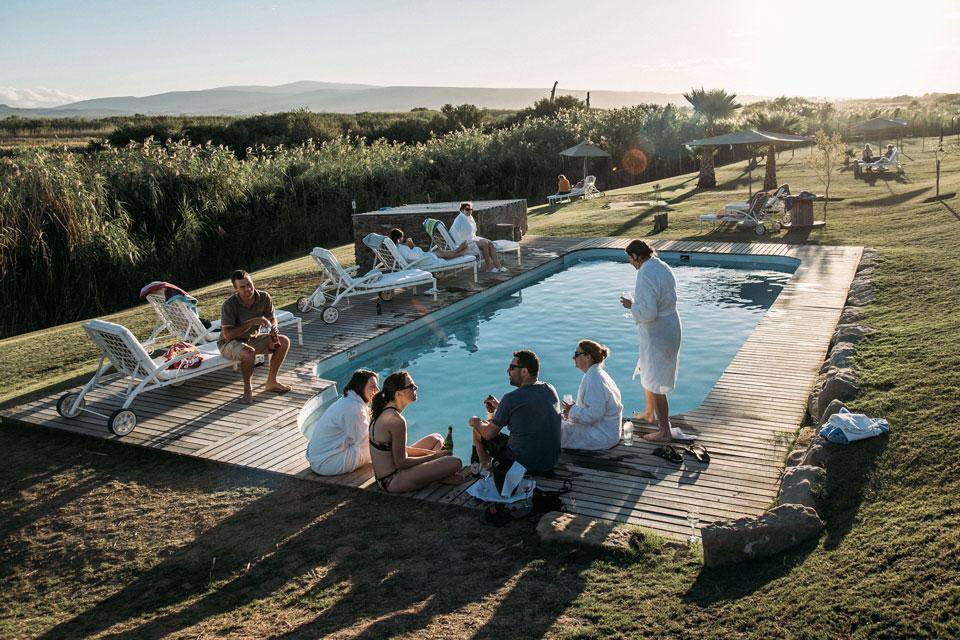 Eine Gruppe junger Leute sitzt am Pool und geniessen das Leben.